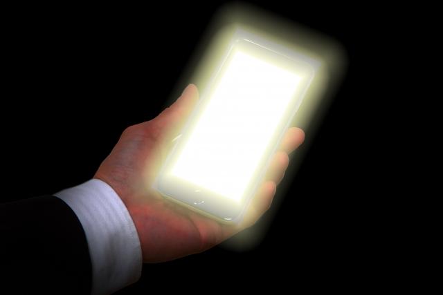 手のひらに光るスマホをもっている写真